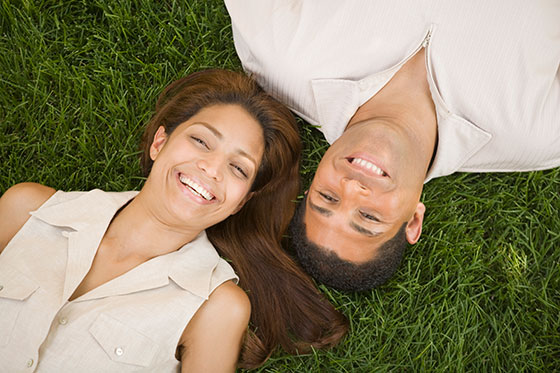a couple laying down on a beautiful lawn.