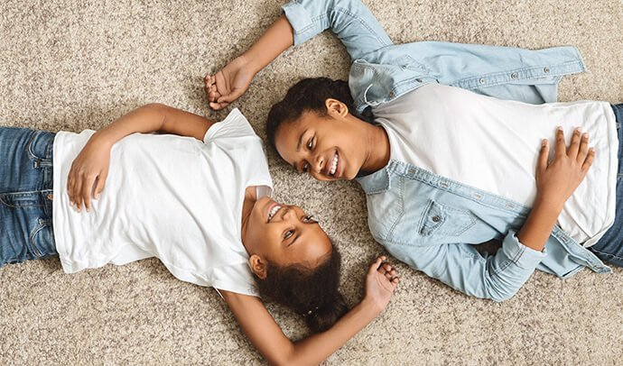 two sisters laying on a fresh carpet.